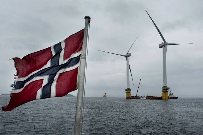 A Norwegian flag flies from a boat near the assembly site of offshore floating wind turbines in the Hywind pilot park, operated by Equinor