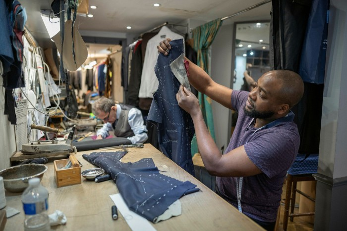Tailor Paul Kitsaros, left, and his apprentice Chuks Ibe have their hands full assisting clients emerging from months of casualwear to return to the office, but their trade could be hit if working from home continues