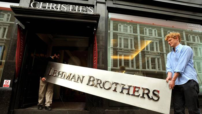 Christie's employees walking into the auction rooms with the main sign from the Lehman Brothers office collection during a photo call at Christie's in west London. PRESS ASSOCIATION Photo. Issue date: Wednesday September 29, 2010