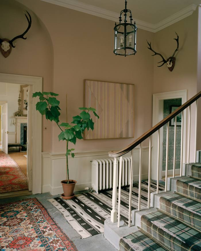 An intricate cut-paper and balsa-wood artwork by Kings hangs in the hallway. The stair runner is the Ogilvy tartan