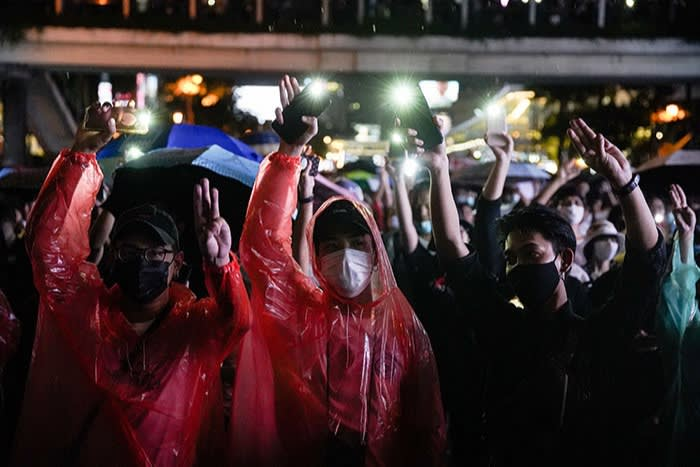 Protesters at a flash demonstration after last month's emergency decree use umbrellas to shield themselves from water cannons fired by the police