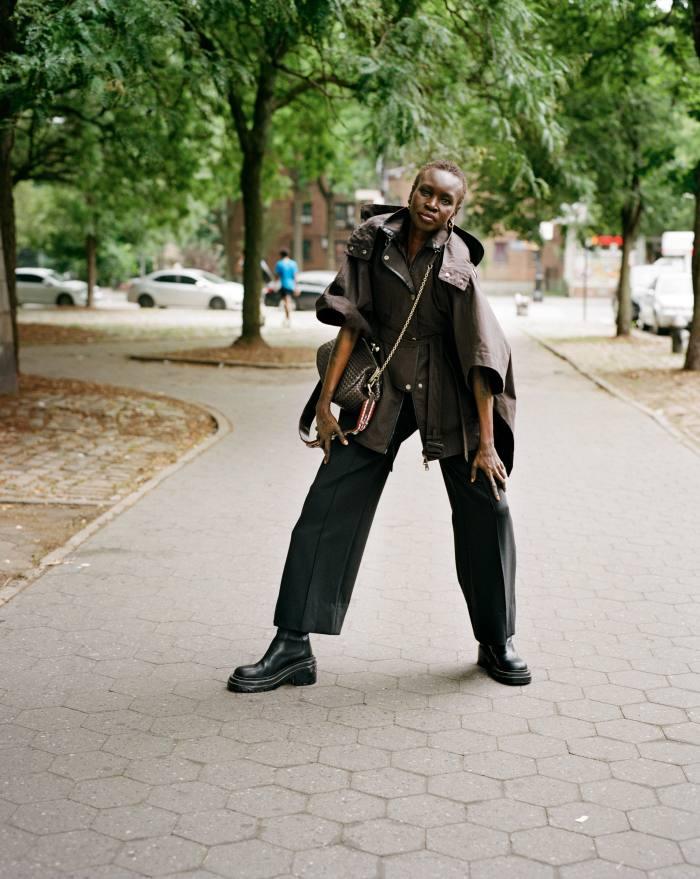 Weekend Max Mara: A.W.ORLD by Alek Wek cotton gabardine poncho jacket, £560, and polyester bag, £350. Proenza Schouler technical wool trousers, POA. Bottega Veneta leather boots, £1,280, and gold hoop earrings, £265