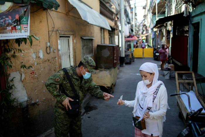 A soldier checks a woman's quarantine pass in Pasay
