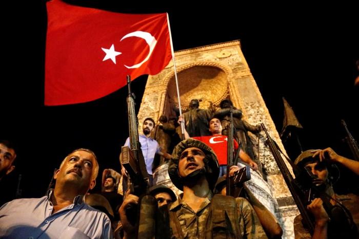 солдаты на площади Таксим в Стамбуле в июле 2016 года. Попытка переворота, совершенная воинственными группировками-изгоями, ознаменовала разрыв в отношениях страны с остальным миром, говорят аналитики © Sedat Suna / EPA