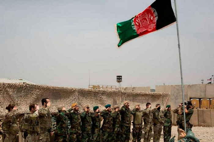 An Afghan flag flies as American and Afghan soldiers salute during a handover ceremony at Camp Anthonic in Helmand province