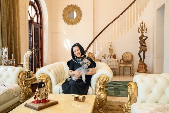 """The designer at home in Beijing with her poodle, Nuomi (""""Sticky Rice"""")"""