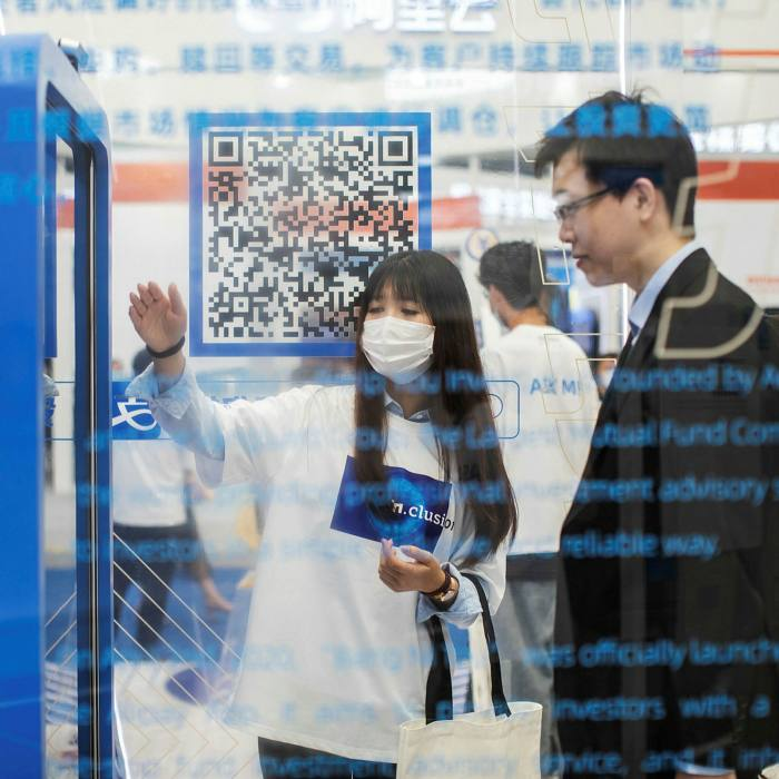 A woman views a QR Code at an Ant Group stall in Shanghai. The move against Alibaba came two months after Chinese financial regulators cancelled Ant's planned $37bn flotation