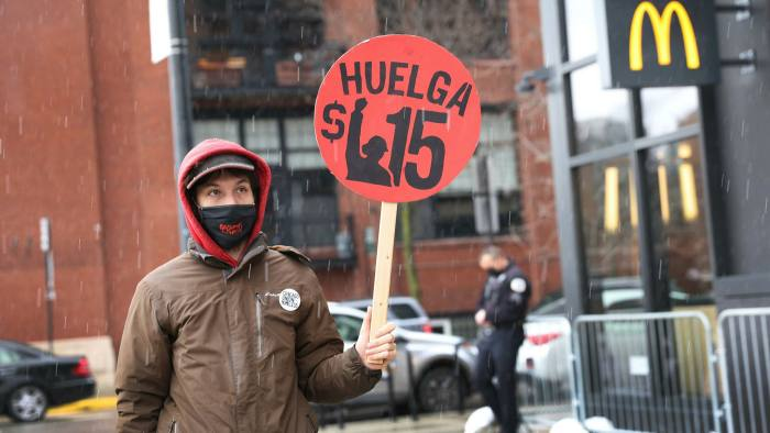 A man protests for a higher minimum wage in Chicago. Governments should also curb practices that drive down labour costs by increasing worker insecurity