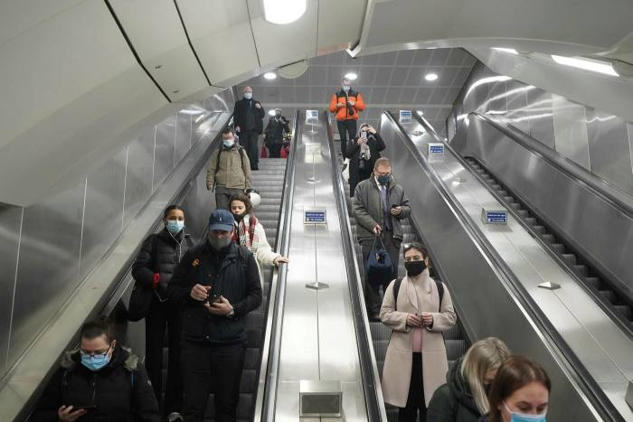 Commuters wearing masks on an escalator at London's Victoria Station. The variant's rapid spread could be due to carriers ignoring social-distancing measures