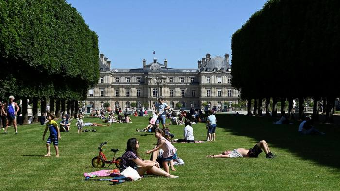 Parisians lie and sit under the sun on the lawns of Jardin du Luxembourg