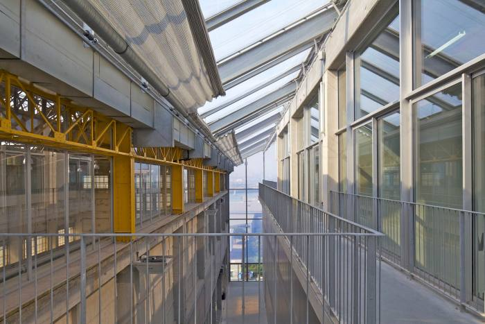The space between the two glass walls of industrial appearance with a glass roof