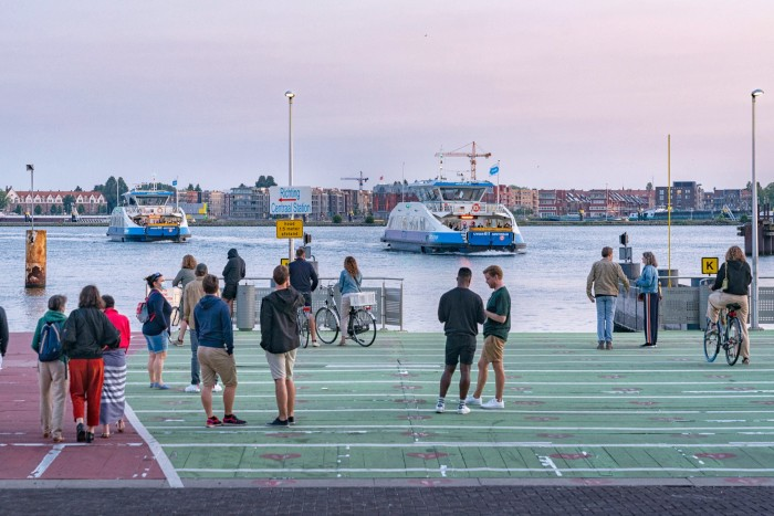 People wait for the ferry to central Amsterdam from the NDSM