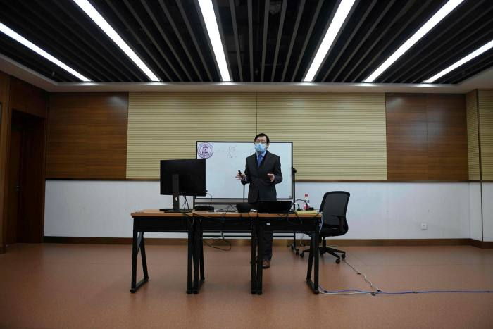 A professor teaches a class online during a government-organized visit to Tsinghua University