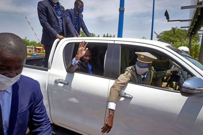 Colonel Assimi Goïta waves from his vehicle after returning from a meeting with Ecowas on Monday