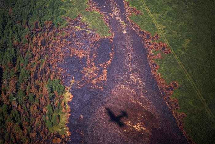 Shadow of an aircraft of the Air Forest Protection Service flying over a burned forest in the Russian Republic of Sakha