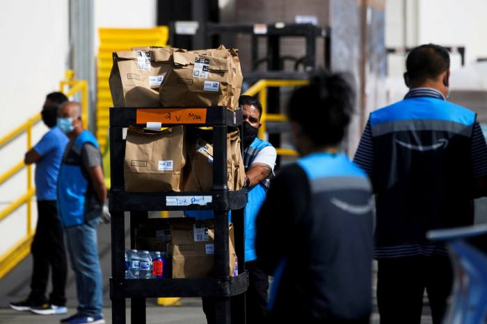 An Amazon delivery driver pushes a grocery cart through a distribution center in Redondo Beach, California