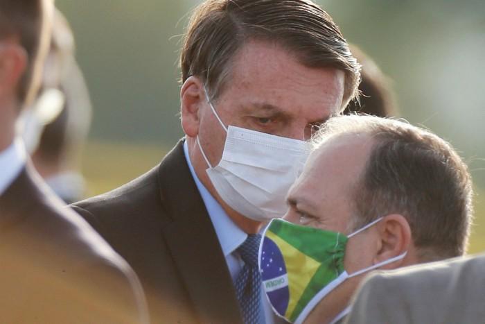 El presidente de Brasil, Jair Bolsonaro, habló con el ministro provisional de Salud, Eduardo Pazuello, la semana pasada antes de una ceremonia para izar la bandera nacional.