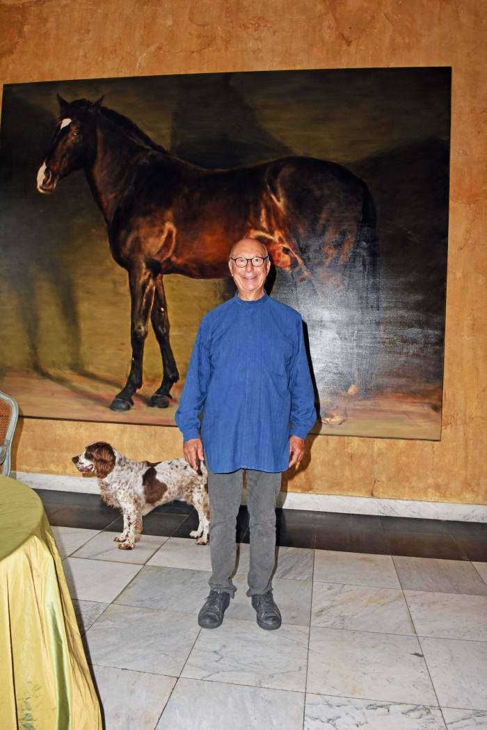 "Axel Vervoordt, pictured at home in 's-Gravenwezel with his springer spaniel Inu, has such affection for his former horse Raio (who died this year), he had him captured in a painting by the artist Michaël Borremans. Now in his 70s, the Belgian designer is still a keen rider. ""I love horses – my father was a horse dealer,"" he says of his regular gallops, which take him across his 62-acre estate."