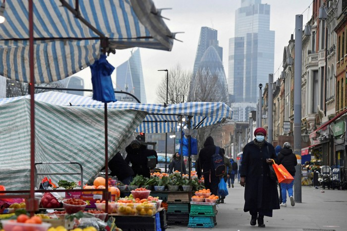 People shop at a market in the shadow of the City of London. Public health experts in the UK say the staged relaxation of restrictions should be timed to keep R number below 1