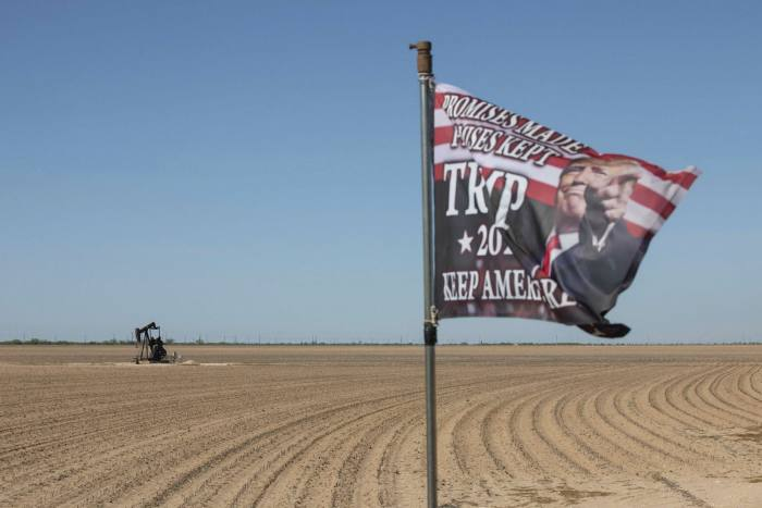 An active pump jack stands past a Trump 2020 flag flying at a private ranch in Midland, Texas, last April. That month West Texas Intermediate, the US benchmark crude contract, traded below zero for the first time