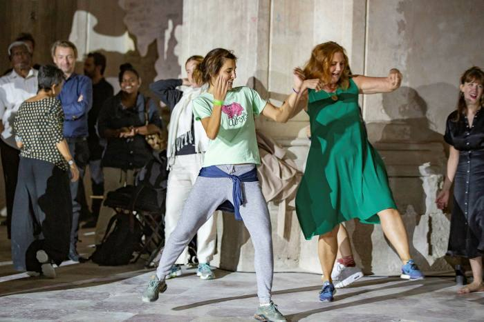Two women are mid-energetic dance move