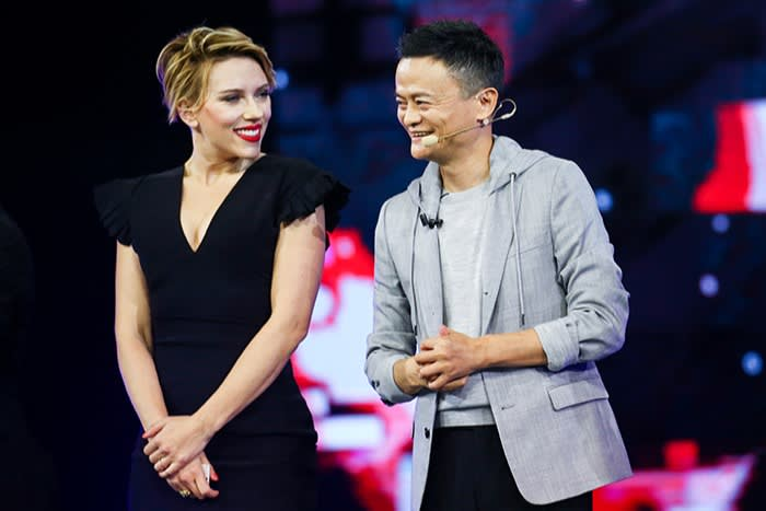 Jack Ma stands on stage next to actress Scarlett Johansson at a promotion for an online shopping festival in Shenzhen in 2016. Both are smiling