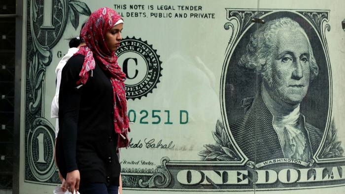 A woman walks past a currency exchange office in Cairo, Egypt