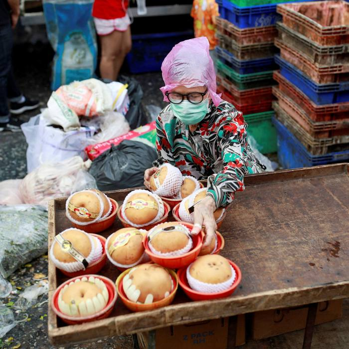A woman wearing a protective mask sells fruit at a market in Bangkok