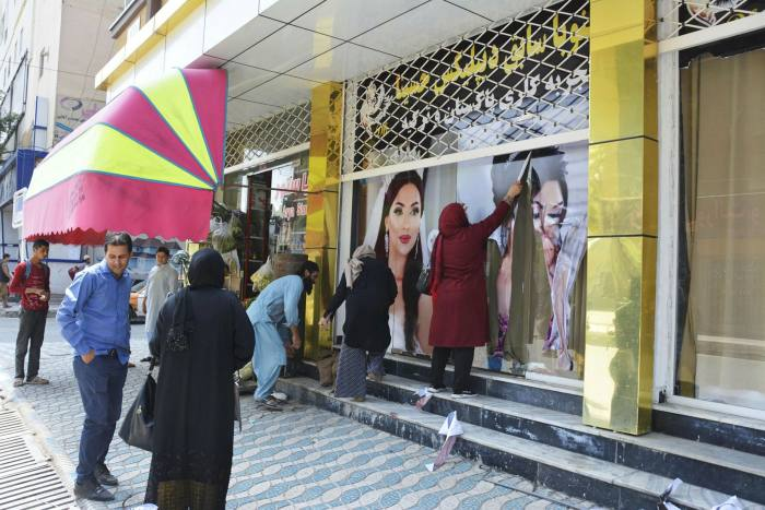 De grandes photos de femmes sont retirées d'un mur dimanche après l'annonce de l'entrée des talibans à Kaboul