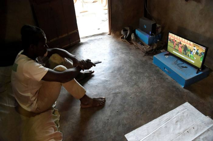 A man watches TV in Togo. Africa's internet cables are increasingly too slow and costly for intensive use of internet resources, such as cloud computing or video streaming