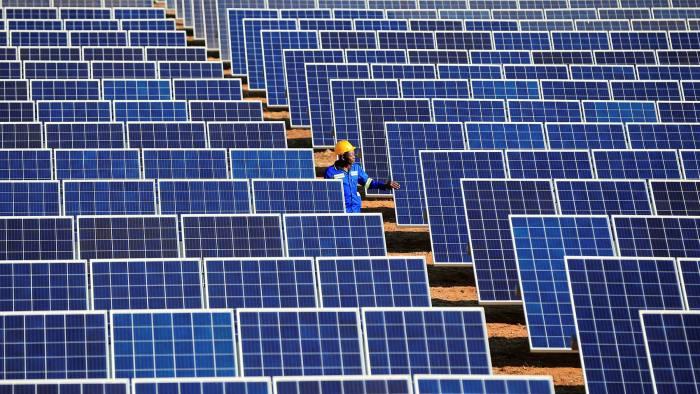 A worker walks between solar panels at Centragrid power plant in Nyabira, Zimbabw