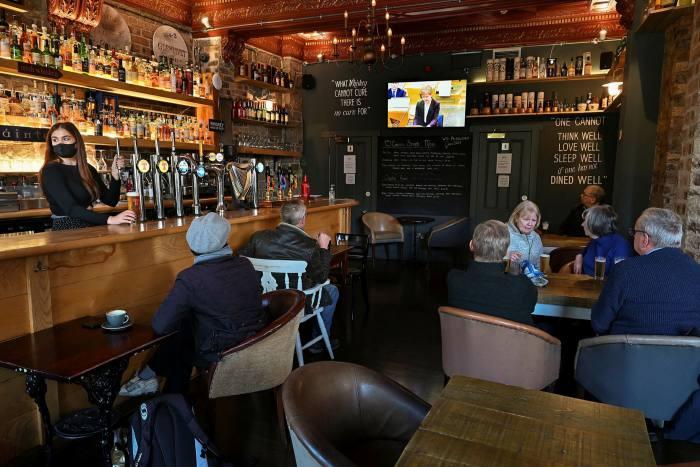 Pub-goers in Edinburgh watch Nicola Sturgeon's announcement on TV on October 7