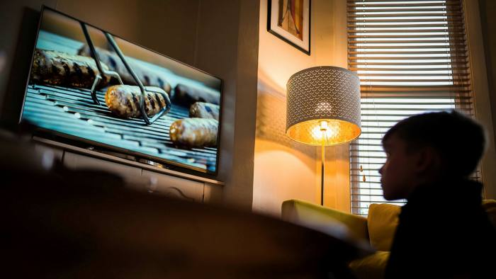 A child watching a TV advert for sausages
