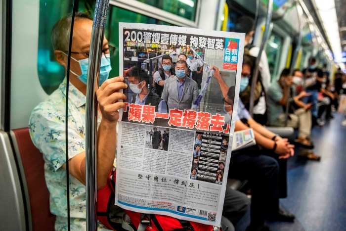 A commuter reads a copy of the Apple Daily newspaper, whose offices were searched last year by police and its founder, Jimmy Lai, arrested under security laws