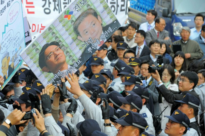 Anti-corruption protesters hold placards of Lee Kun-hee and Lee Jae-yong in Seoul in 2008. The father and son faced charges stemming from allegations of shady financial dealings in order to hand control of the Samsung empire from one generation of the founding family to the next