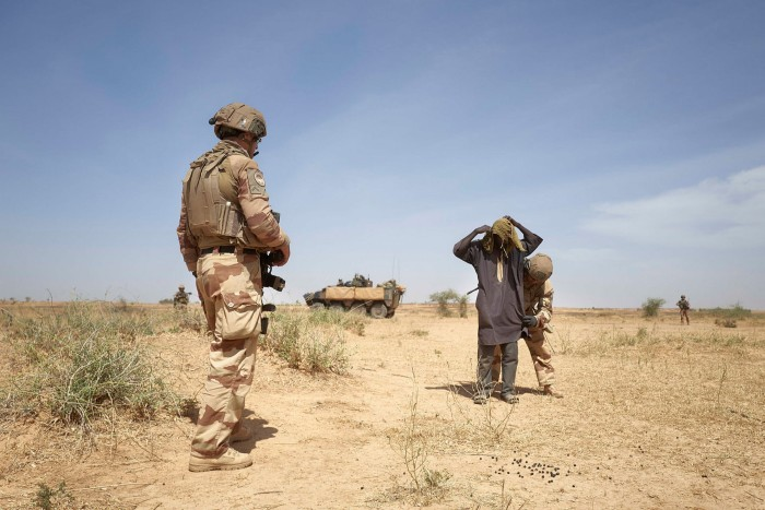 A Burkinabe herder is searched by a French soldier as a suspected jihadi collaborator