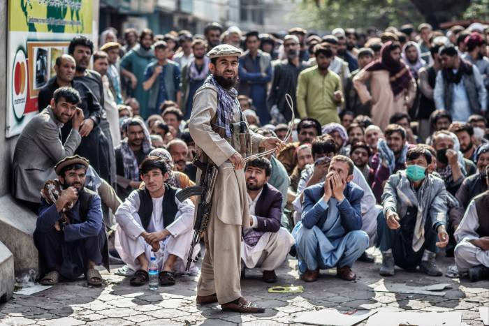 A Taliban soldier with a whip serves as a security guard outside a bank while men wait for cash