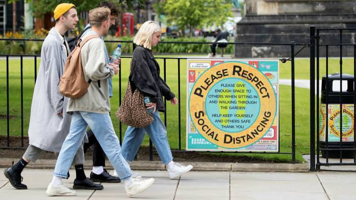 People walk past a sign at St Andrews Square in Edinburgh reminding the public of social-distancing rules