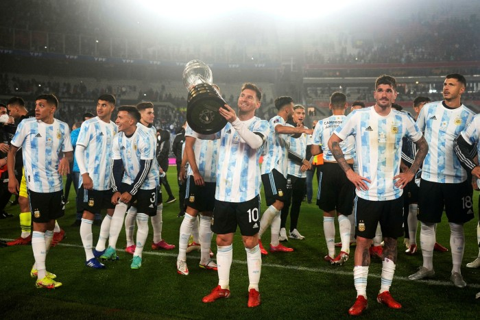 Argentina's Lionel Messi, center, holds the Copa America trophy at the end a qualifying soccer match for the FIFA World Cup Qatar 2022