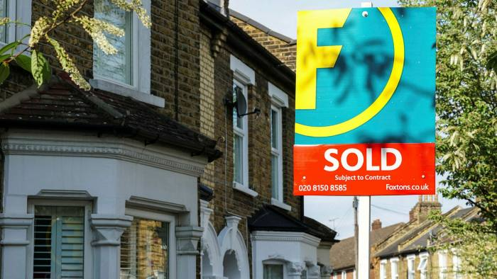 Sold sign outside terraced houses in London, England