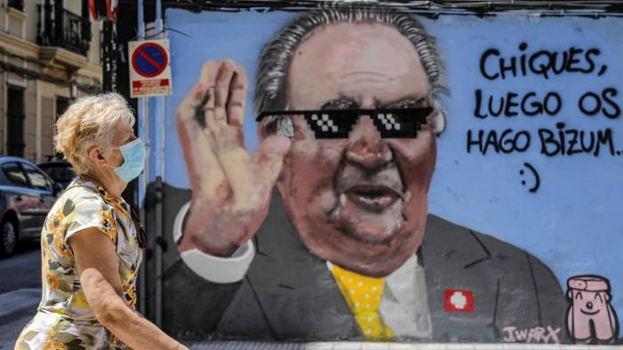 A woman walks past graffiti in Valencia depicting the country's former king Juan Carlos, who announced this week he was to 'leave Spain'