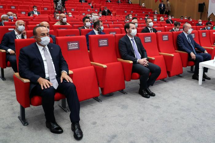 Turkey's president Recep Tayyip Erdogan, right, with finance minister Berat Albayrak, centre. Mr Erdogan has praised measures taken to block 'malicious' attacks on the lira
