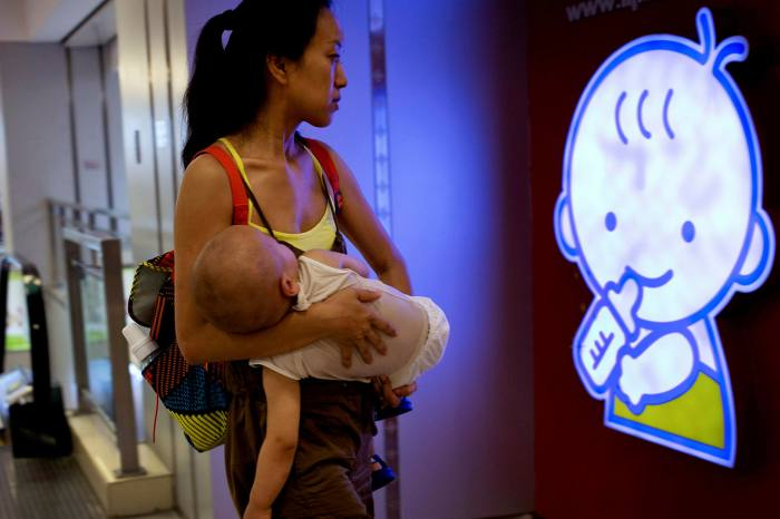 A woman carrying her baby at a shopping mall in Beijing, China