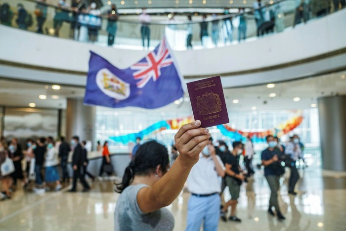 A demonstrator shows a British National (Overseas) passport as another waves a colonial-era Hong Kong flag during a lunchtime protest at the International Finance Center shopping mall in Hong Kong last week