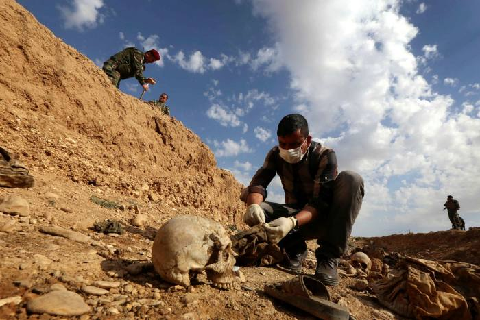 An Iraqi examines the remains of members of the Yazidi religious minority killed by Isis at a mass grave near the village of Sinuni, Sinjar, in Iraq