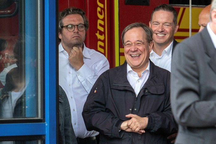 North Rhine-Westphalia's State Premier and CDU's candidate for Chancellery Armin Laschet laughs while the German President delivers a speech when they visited flood-devastated areas of western Germany
