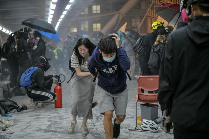 Hong Kong protesters run for cover as police fire tear gas on a university campus in November 2019