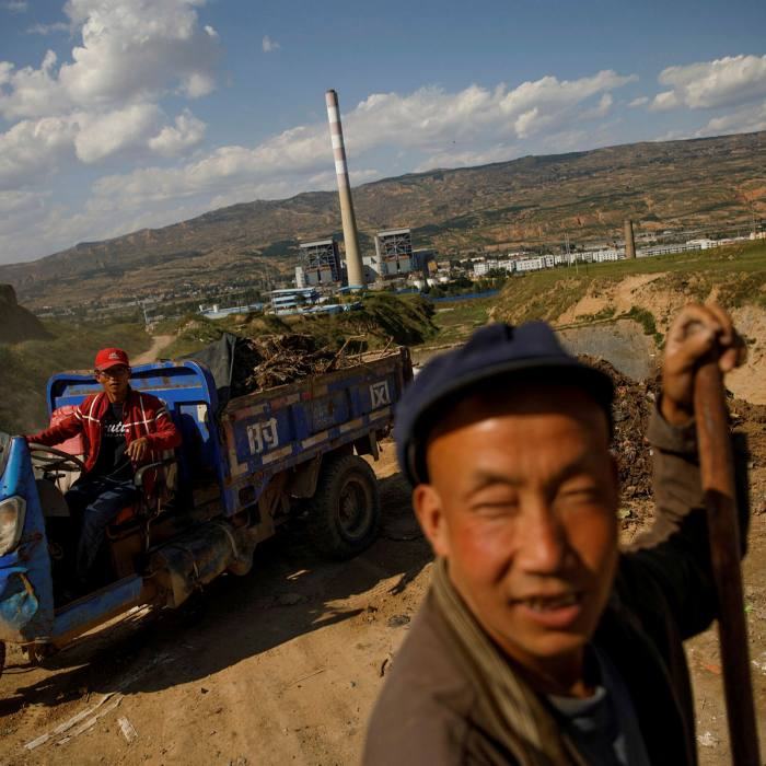 Workers unload rubbish into a landfill near the decommissioned Gangu coal-fired power plant in Maojiaping village, Gangu County, Gansu
