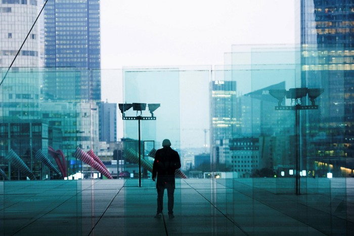 A commuter walks through La Defense in Paris. By the end of 2020, some 2,500 jobs and €170bn in assets had shifted from London to the French capital