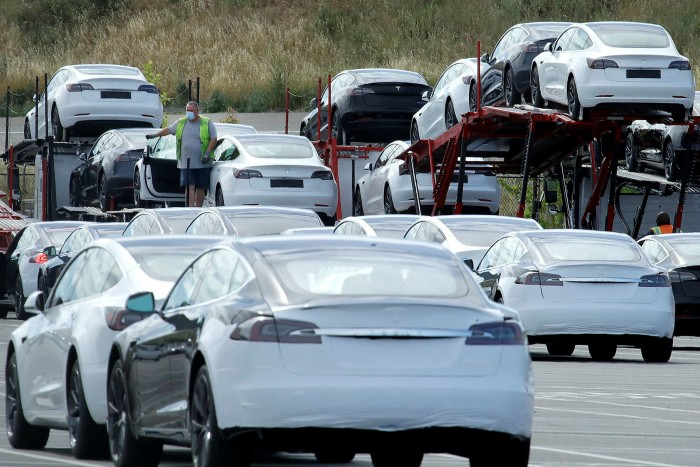 Tesla cars are loaded on to carriers in California. Encouraged by the cleaner air evident in the coronavirus lockdown, the treacle-like shift towards battery cars may pick up pace